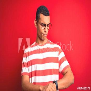 Young handsome african american man wearing casual striped t-shirt and glasses Checking the time on
